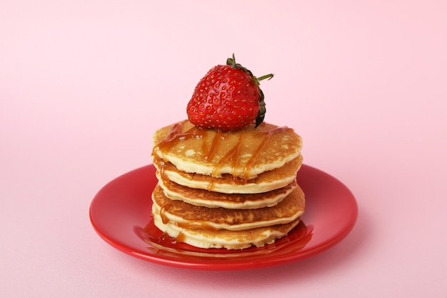 Plate with pancakes with strawberry and caramel on pink background