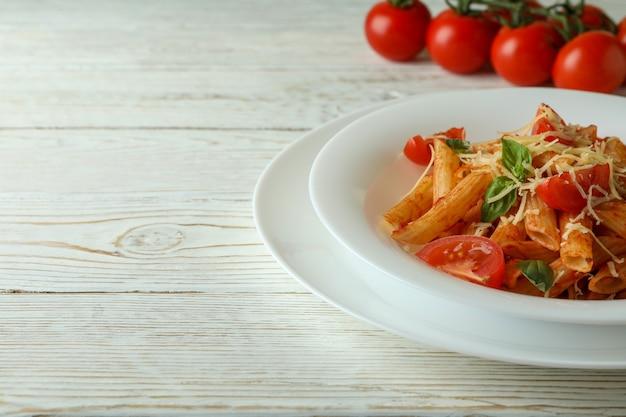 パスタとトマトソースのプレート、白い木製のテーブルにトマト