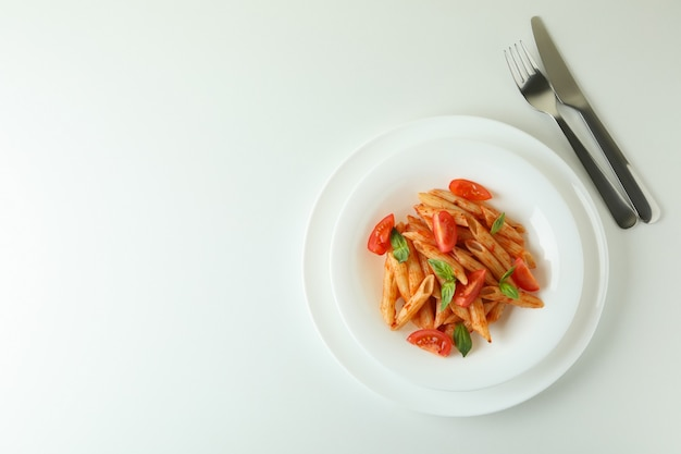 Plate with pasta with tomato sauce on white isolated background