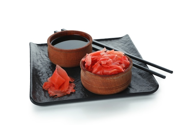 Plate with pickled ginger, soy sauce and chopsticks, isolated on white
