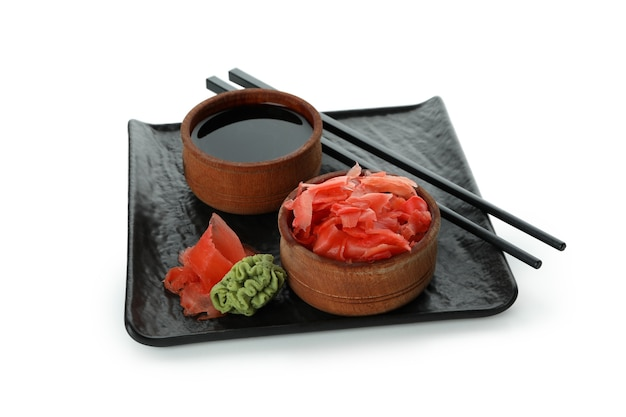 Plate with pickled ginger, soy sauce, chopsticks and wasabi isolated on white surface