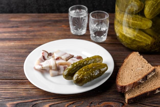 Тарелка с солеными огурцами и беконом