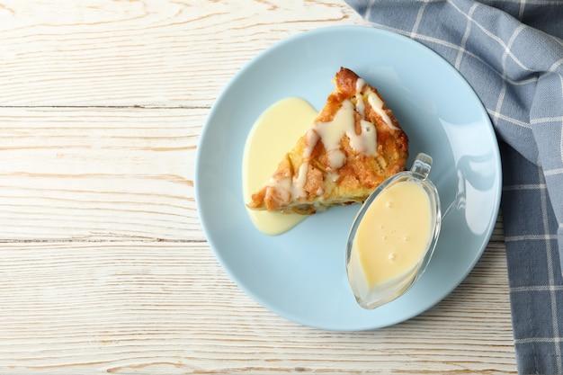 주방 수건으로 나무 배경에 파이와 연유와 접시