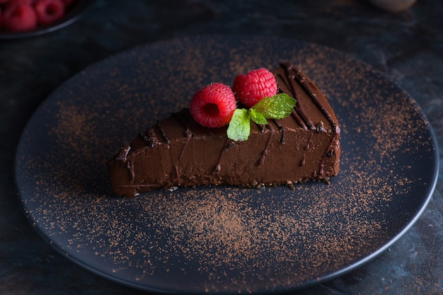 A plate with a piece of chocolateberry sponge cake on a gray table dessert with fresh berries