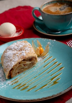 Plate with piece of delicious slice of an apple strudel and cup of coffe on the table