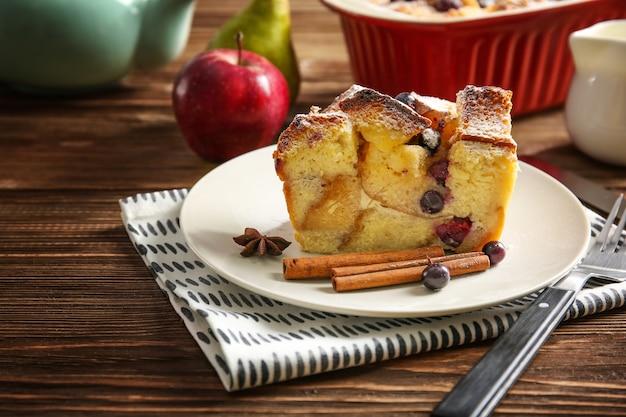 나무 테이블에 맛있는 빵 푸딩이 있는 접시