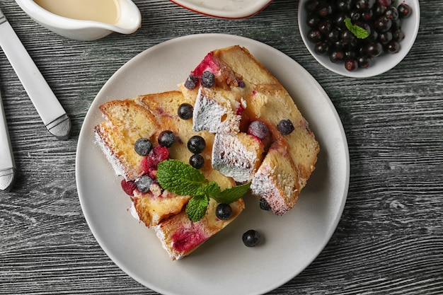 나무 테이블에 구운 빵 푸딩 조각이 있는 접시