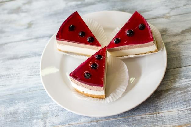 케이크 조각으로 접시. 디저트 위에 딸기. 건포도 젤리와 치즈 케이크. 3명의 손님을 위한 대접.