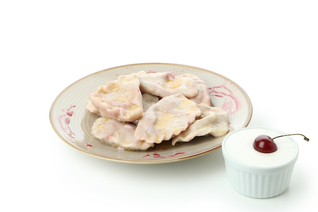 Plate with pierogi with cherry isolated on white background