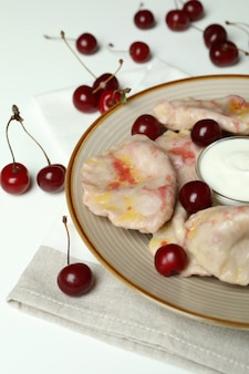 Plate with pierogi with cherry on kitchen towel on white background