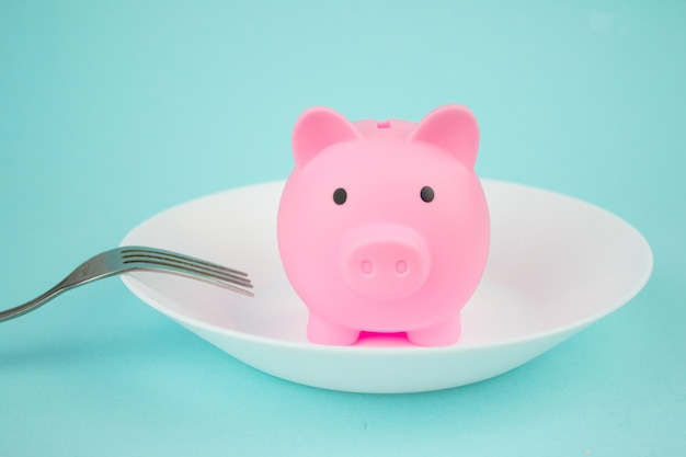 Plate with piggy bank with fork on blue background, savings consumer concept