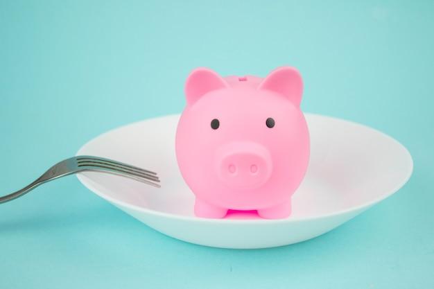 青い背景の上の貯金箱、節約消費者の概念とプレート