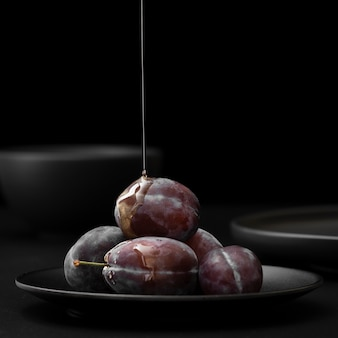 Plate with plums and honey on a dark background