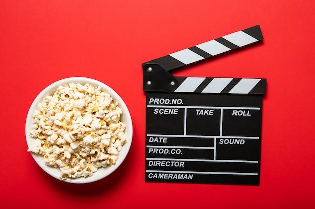 赤い背景の上のポップコーンと映画のクラッパーボードプレート