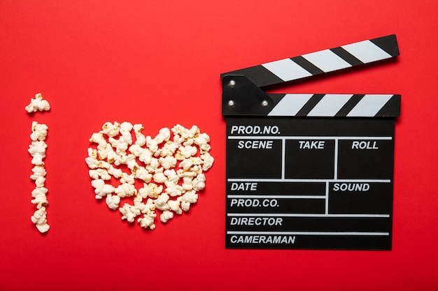Plate with popcorn and movie clapper board on a red background