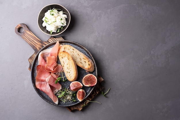 Plate with prosciutto antipasto, toast, ricotta on a cutting board on a gray background, ham snack.
