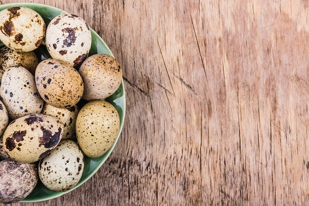 Plate with quail eggs on wooden board