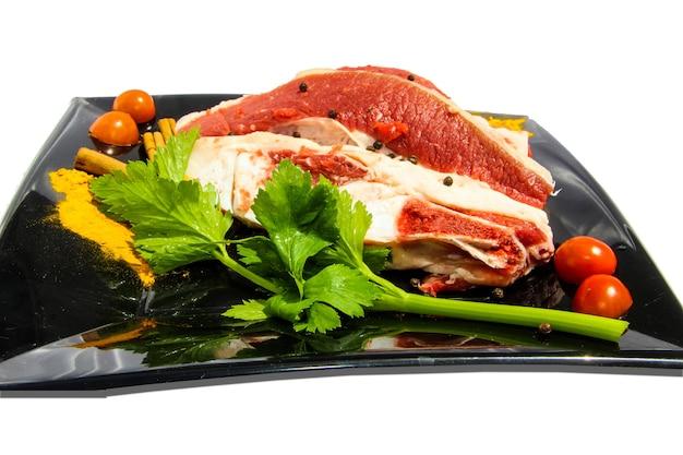 白い背景、孤立したオブジェクトの周りに生肉と食品の装飾が施されたプレート