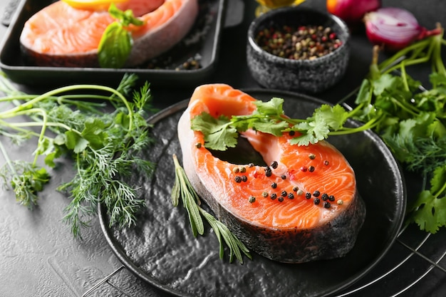 Plate with raw salmon steaks, herbs and spices on dark