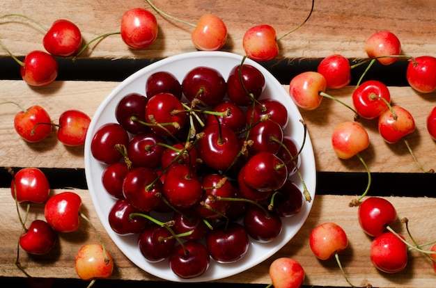 Plate with red cherries on wooden plates, yellow and red cherry, top view