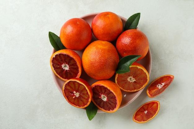 Тарелка с красными апельсинами и листьями на белом текстурированном