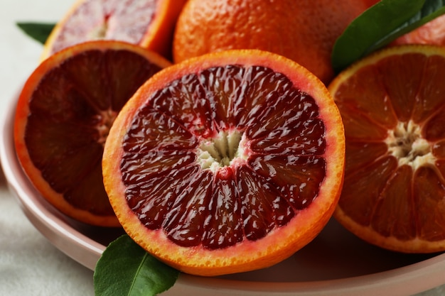 Plate with red oranges and leaves, close up