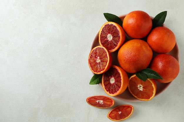 Plate with red oranges and leaves on white textured isolated background