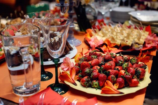 잘 익은 딸기와 접시입니다. 아름다운 축제 테이블 설정입니다. 선택적 초점입니다.