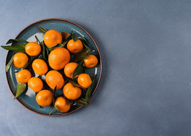 Тарелка со спелыми мандаринами с копией пространства на сером фоне