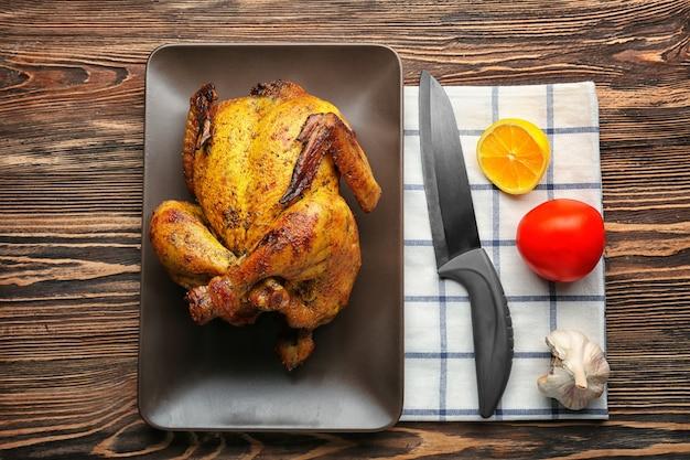 Тарелка с жареным пивом может курица на деревянных фоне