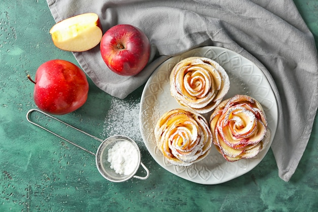 テーブルの上にバラの形をしたリンゴのペストリーとプレート