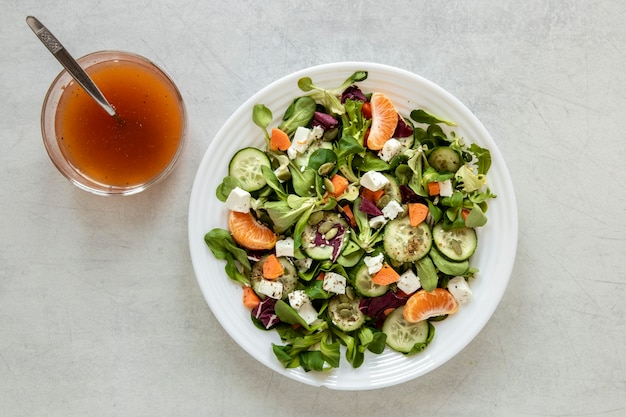 Plate with salad and bowl with souce