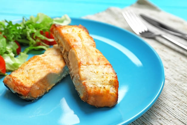 Plate with salad and delicious slices of salmon, closeup