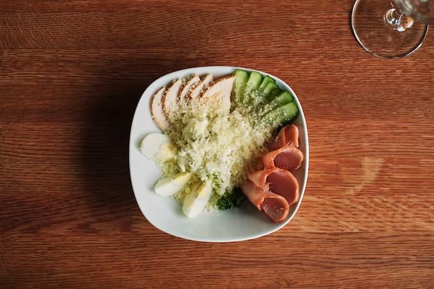 Plate with salad ham eggs vegetables on dark wood background