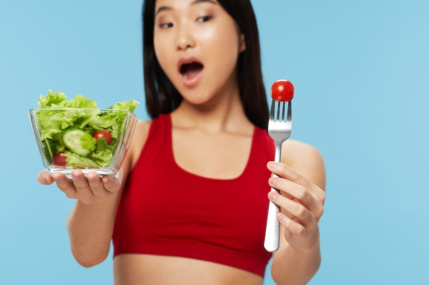 Plate with salad healthy food lifestyle diet woman with a slender figure of asian appearance fork with cherry tomato