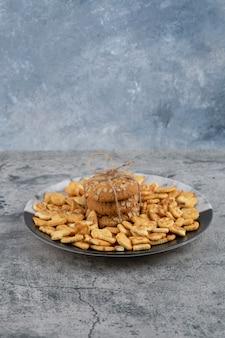 Тарелка с солеными крекерами и овсяным печеньем на мраморном фоне.