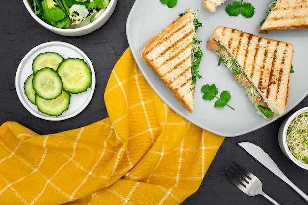 Тарелка с бутербродами и ломтиками огурца