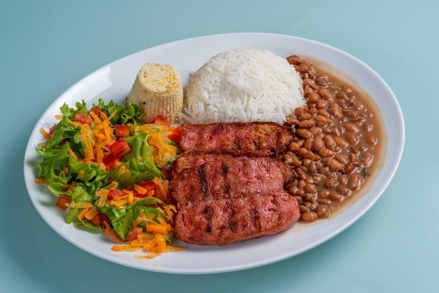 ソーセージビーンズライスサラダとファロファの伝統的なブラジル料理のランチを添えたプレート