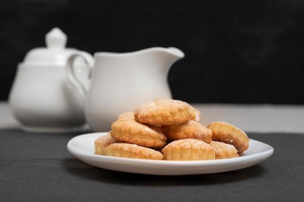 Тарелка с песочным пирогом на фоне чайника и кувшина. домашнее песочное печенье. выпечка к чаю.