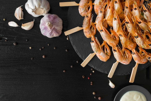 Plate with shrimps skewers and garlic