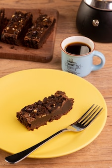 Plate with a slice of brownie, a coffee maker and a cup of coffee.