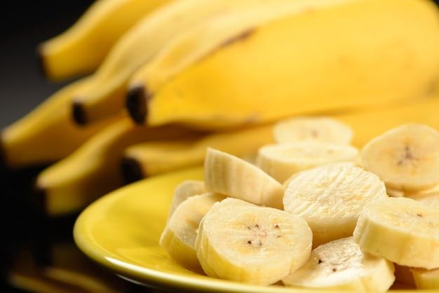 Тарелка с нарезанным бананом на темном столе