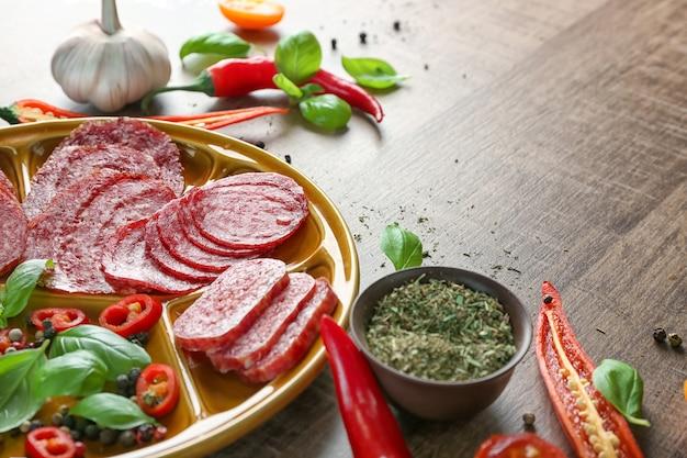Тарелка с нарезанными разными колбасами и специями на столе