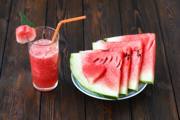 Plate with slices and glass of watermelon smoothie, wooden table
