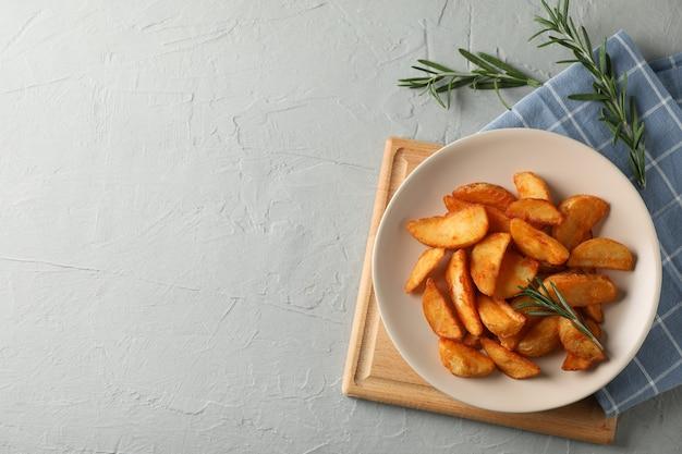 구운 된 감자 웨지, 회색에 냅킨 조각으로 접시. 평면도