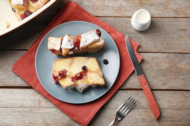 나무 테이블에 빵 푸딩 조각이 있는 접시