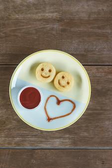 Тарелка с улыбающимся картофелем и кетчупом