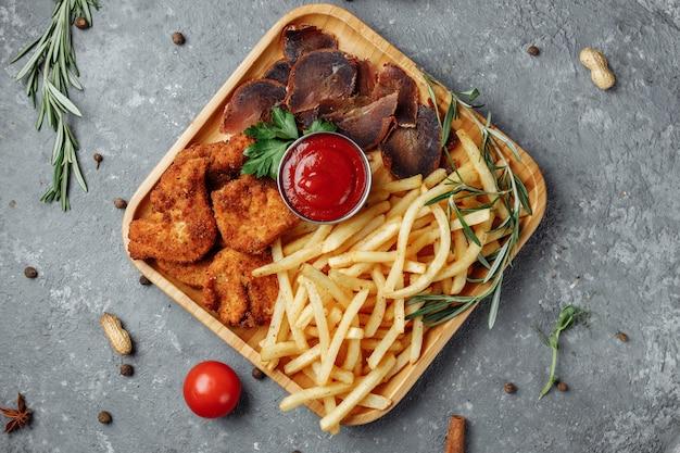 Тарелка с закусками. панированные куриные наггетсы, жареный картофель и хамон.