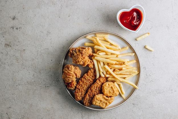 Тарелка с закусками на каменном фоне, самородки, крылышки, полоски и картофель фри с кетчупом, вид сверху с копией пространства