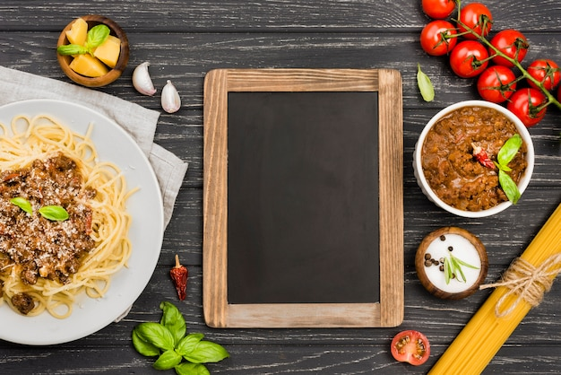 Plate with spaghetii bolognese and chalkboard